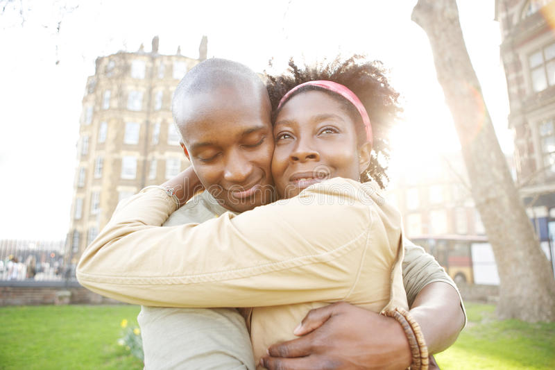 Couple sunset city. Young black couple hugging in a park at sunset, while visiting London city stock image