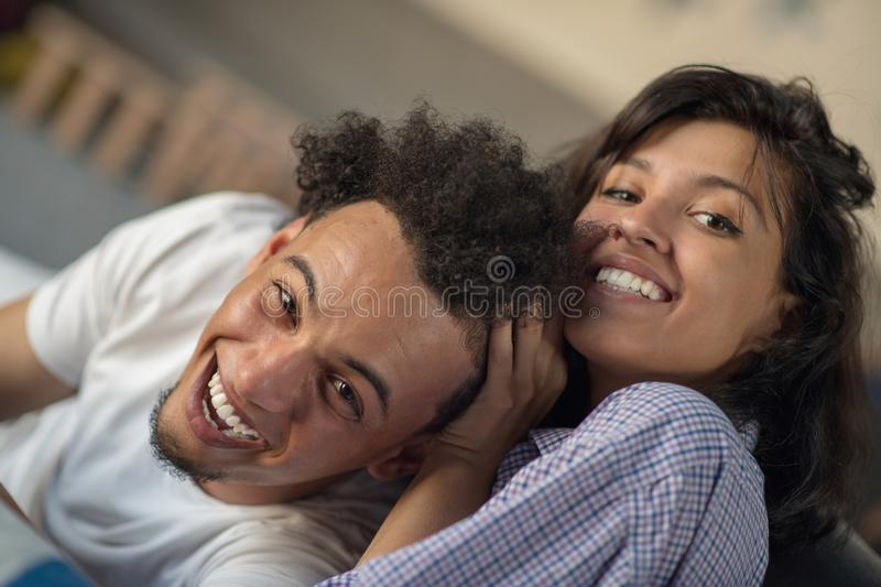 Young black couple relaxing on couch and smiling at camera.  royalty free stock photography