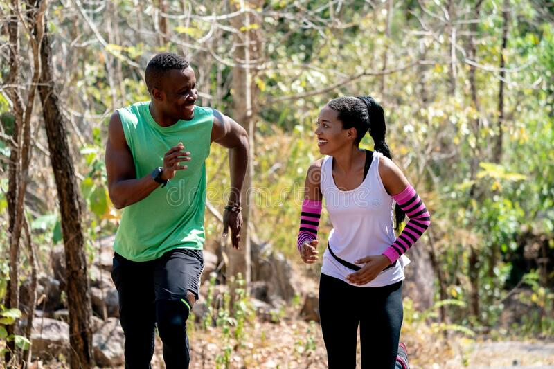 Young Black Couple Running at Forest Trail stock photo