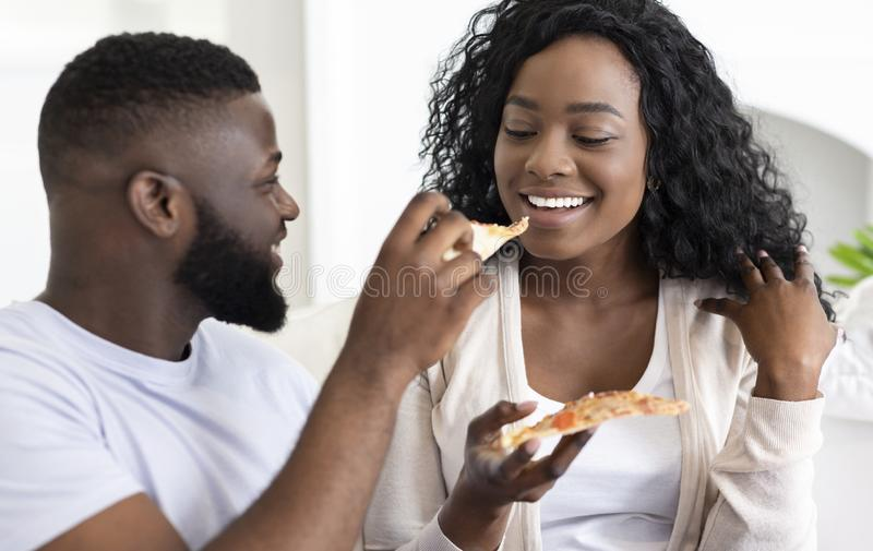 Young black couple sharing pizza on date at home royalty free stock photography