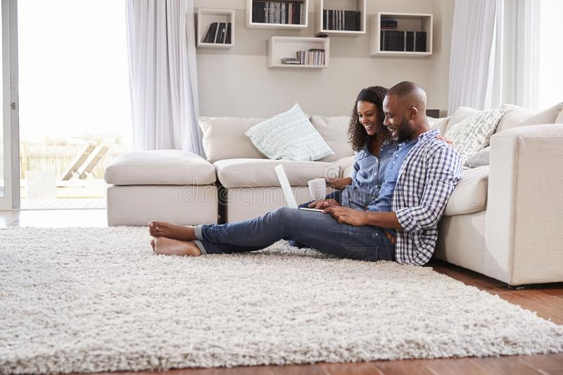 Young black couple sit on the floor using laptop, side view royalty free stock photography