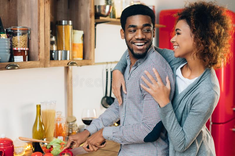 Young black family cooking dinner together in kitchen. Young african-american family cooking dinner together, girl embracing her husband, copy space royalty free stock photos