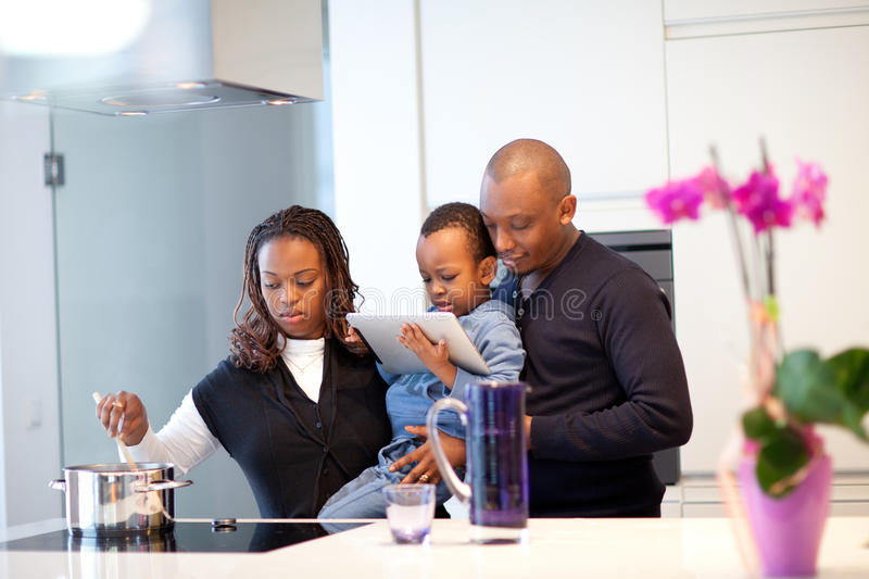 Young black family in fresh modern kitchen royalty free stock photography