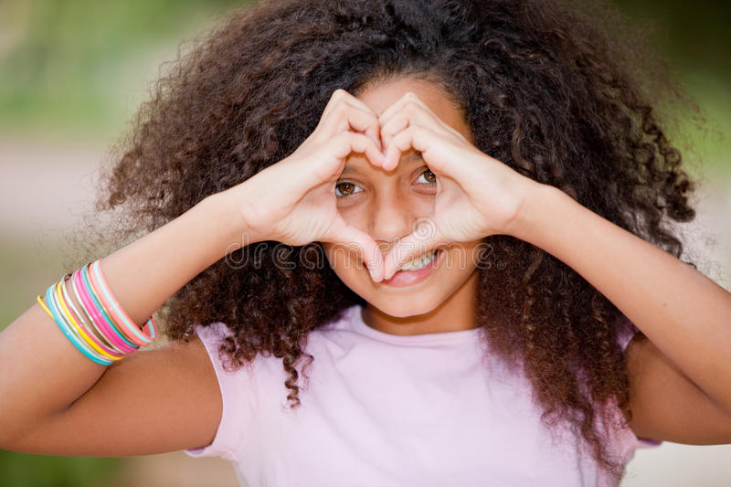Young black girl. Young happy smiling black girl making heart shape royalty free stock image