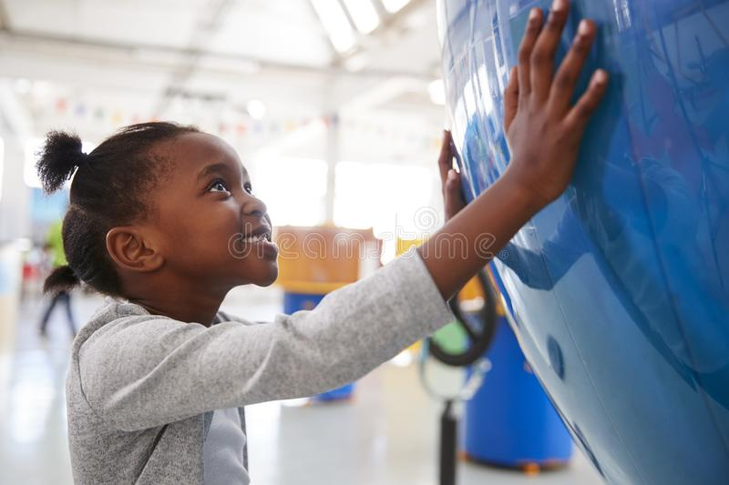 Young black girl holding a giant globe at a science centre royalty free stock images