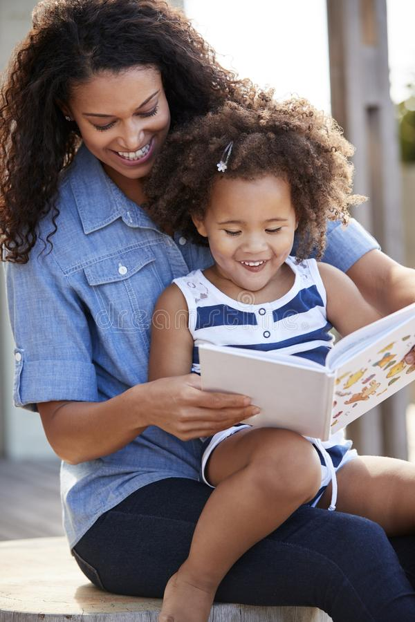 Young black girl reading book sitting on mum�s knee outdoors royalty free stock photography