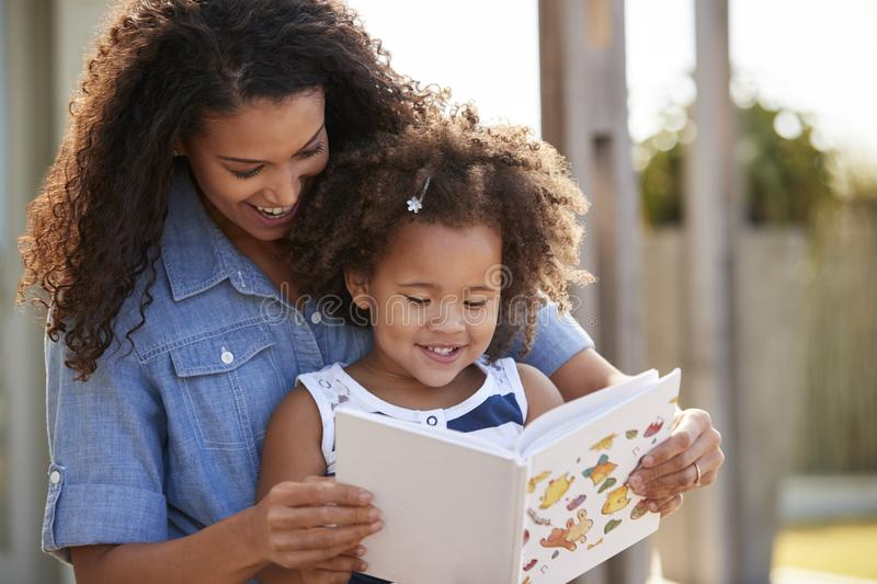 Young black girl reading book sitting on mum�s knee outdoors royalty free stock image