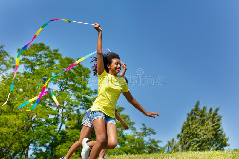 Young black girl run with ribbon over blue sky. Beautiful young black girl run with ribbon over blue sky royalty free stock photo