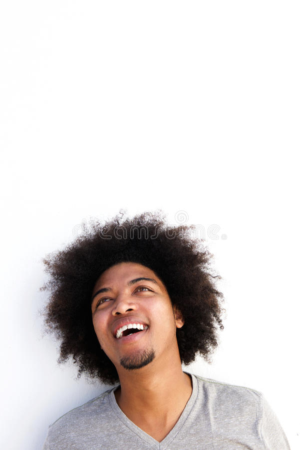 Young black guy with afro laughing and looking up stock photography