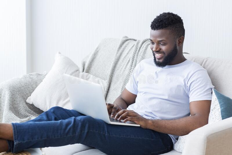 Young black guy chatting online on laptop at home royalty free stock photo