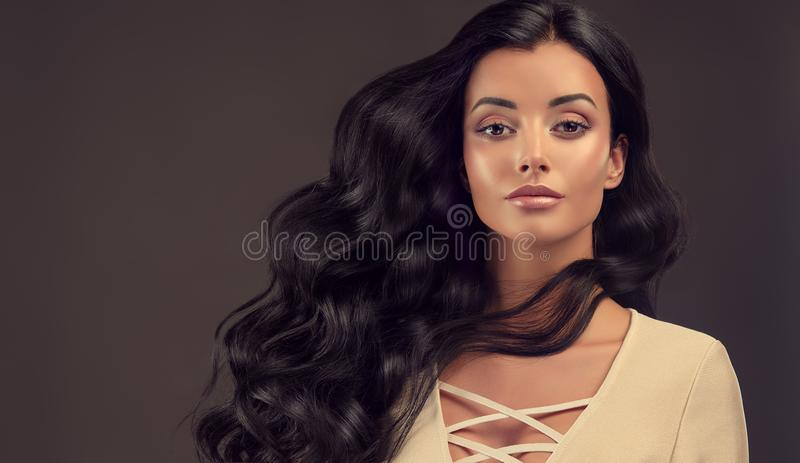 Young black haired woman with voluminous, shiny and wavy hair royalty free stock photo