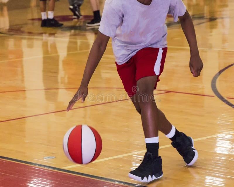 Dribbling a basketball indoors. A young black male is dribbling a basketball indoors during summer basketball camp royalty free stock photo