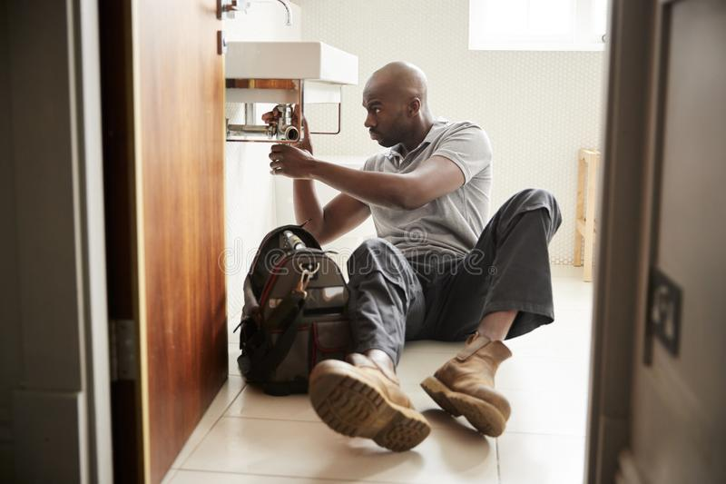 Young black male plumber sitting on the floor fixing a bathroom sink, seen from doorway, full length stock photo