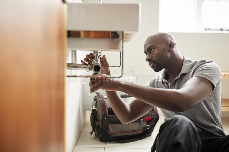 Young black male plumber sitting on the floor fixing a bathroom sink, seen from doorway stock photography