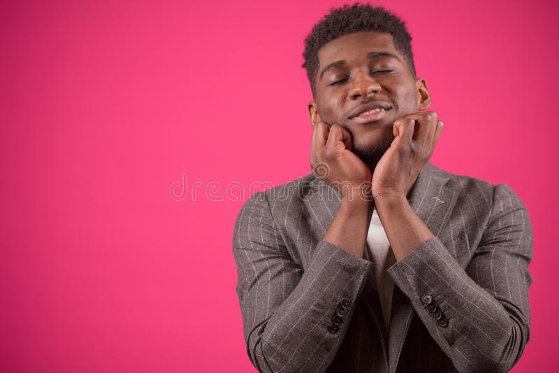 Young black man with closed eyes is touching his chin with hands stock photography