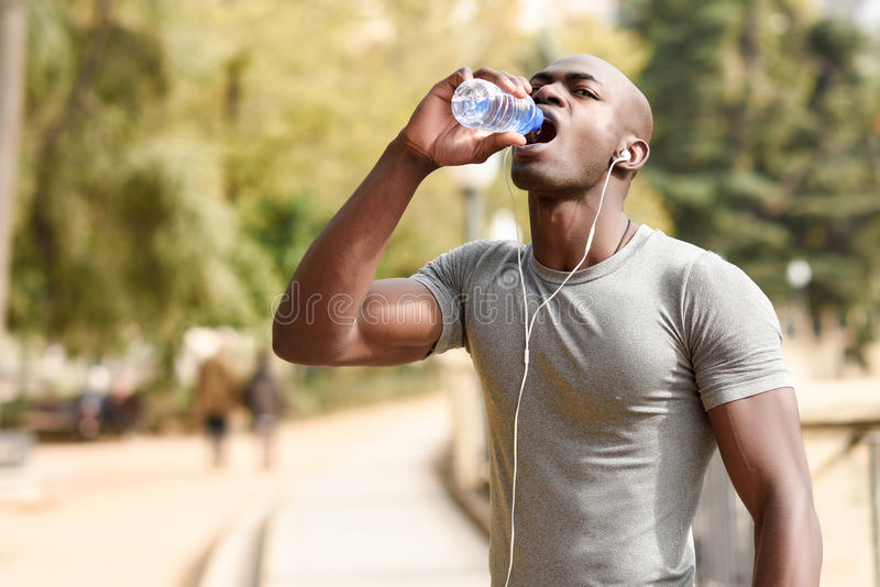 Young black man drinking water before running in urban background stock image