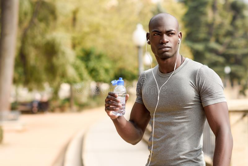 Young black man drinking water before running in urban background stock photos