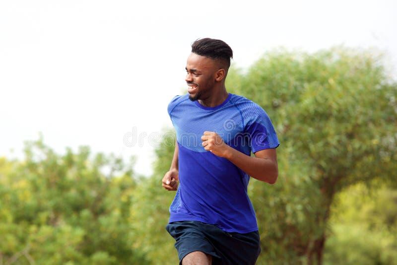 Young black man enjoying his run outside. Portrait of young black man enjoying his run outside royalty free stock photography