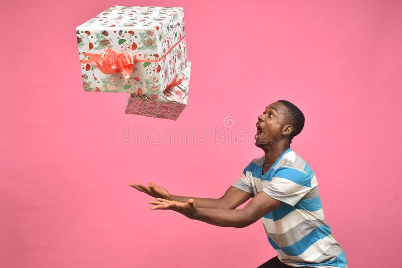 young black man feeling excited while catching gift boxes royalty free stock photos