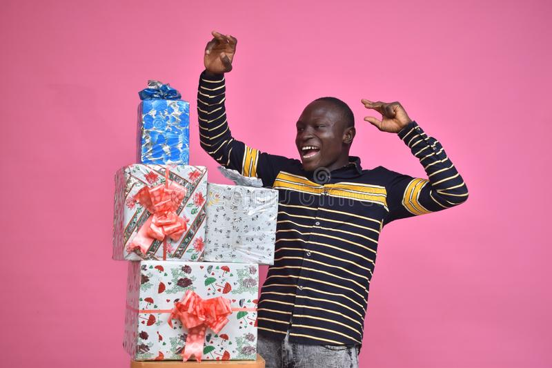 young black man feeling excited and happy and delighted, celebrating while standing next to a stack of gift boxes with fists in royalty free stock photos