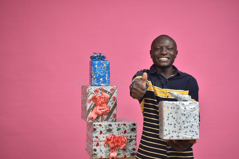 young black man feeling excited while holding a gift box in one hand doing a thumbs up gesture stock photos