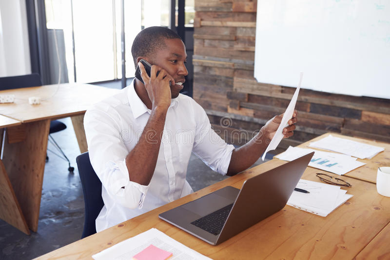 Young black man in office holding document using smartphone royalty free stock photography