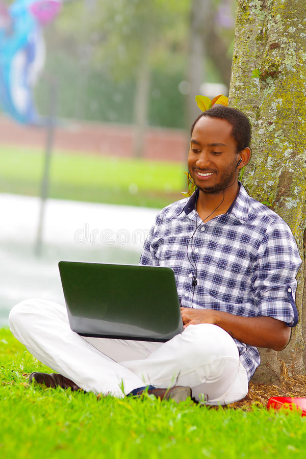 Young black man sitting down on green grass and working in his computer posing his back in a tree in the city of Quito royalty free stock photo