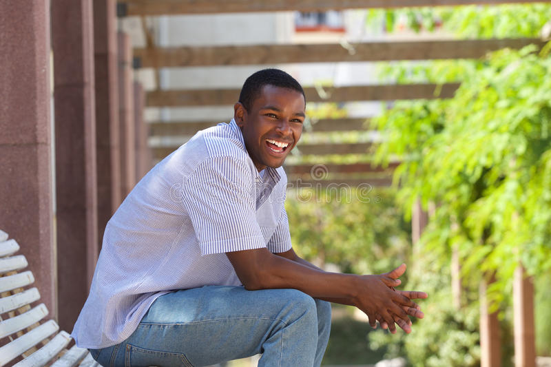 Young black man sitting outside laughing stock photography