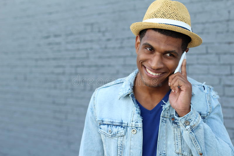 Young black man smiling and talking on mobile phone outside with copy space on the left royalty free stock photo