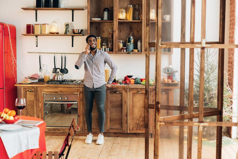 Young black man talking on mobile phone in kitchen stock photo