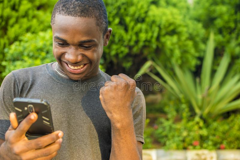 young black man viewing content on his phone feeling excited and happy and celebrates stock photo
