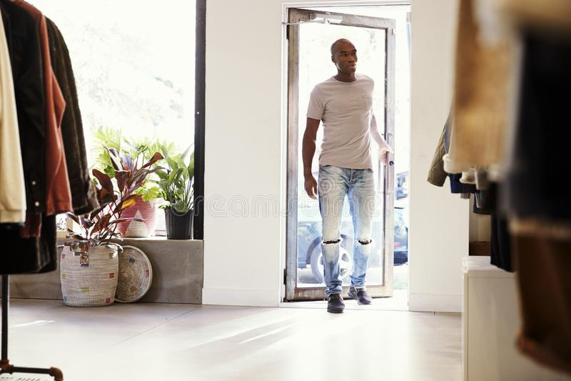 Young black man walking into a clothes shop and closing door stock images