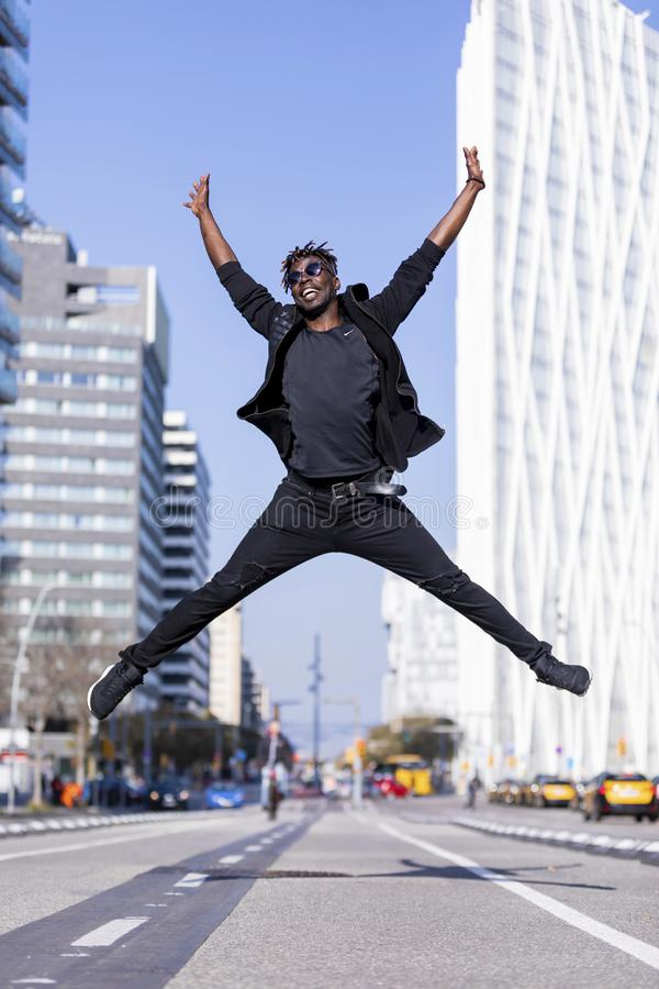 Young black man wearing casual clothes jumping in urban background. Lifestyle concept. Millennial african guy wearing sunglasses stock image