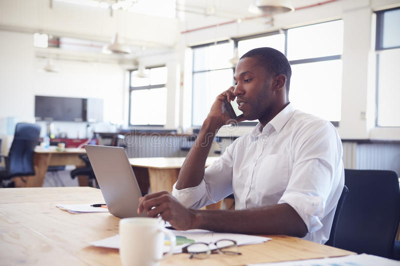 Young black man working in office with laptop using phone royalty free stock photography