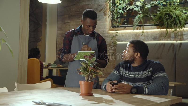Waiter taking order working in cafeteria. Young black men in apron walking in cafeteria and taking notes of order talking to client royalty free stock images