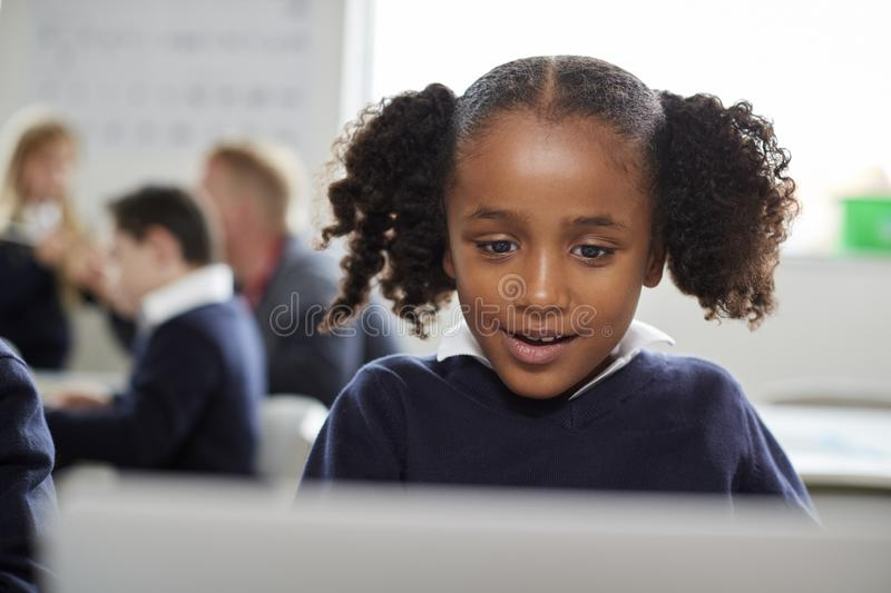 Young black schoolgirl using a laptop computer sitting at desk in a primary school classroom, front view, close up stock photos