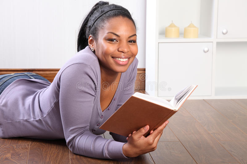 Young black student girl reading book at home royalty free stock photography