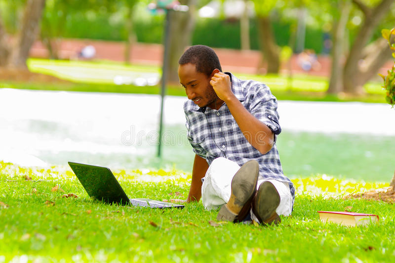 Young black tourist man sitting down on green grass, listening music with his headphones and checking his computer in stock photos