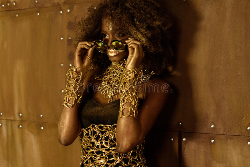 Young black woman with afro hair wearing gold accessories and makeup putting on sunglasses, looking away stock photos