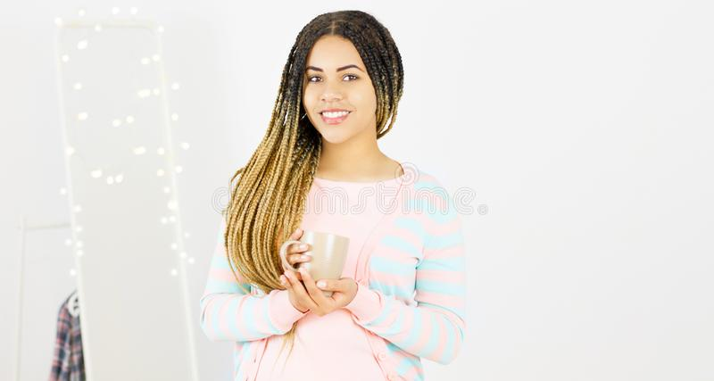 Young black woman with afro hairstyle smiling. Girl with cup hot drink wearing pink dress. Studio shot royalty free stock photography