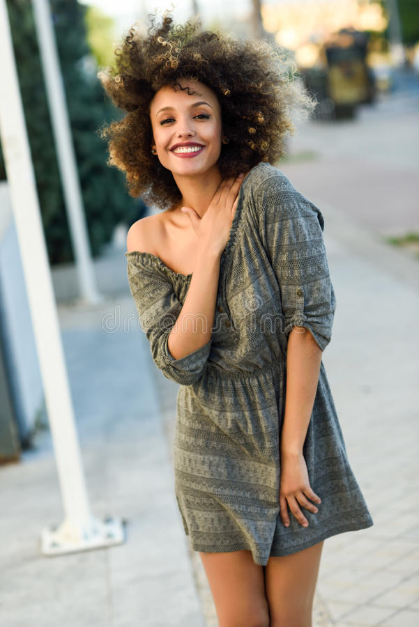 Young black woman with afro hairstyle smiling in urban background stock photography