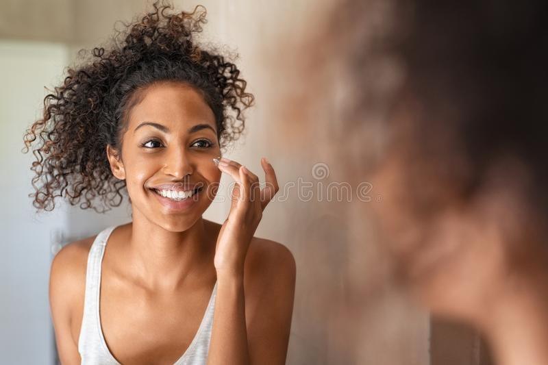 Young black woman applying skin cream royalty free stock photography