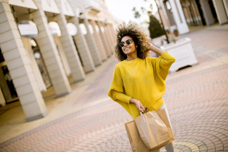Young black woman with curly hair in shopping stock images