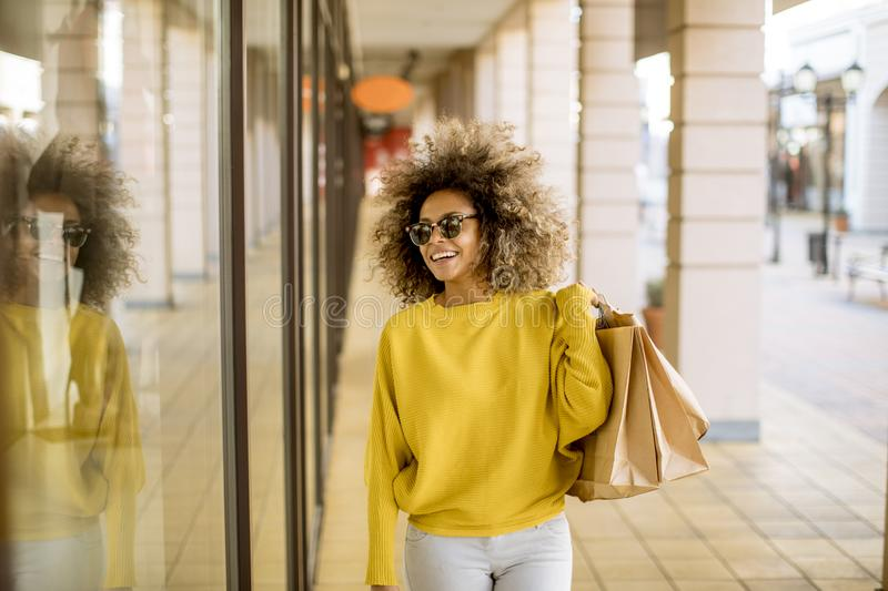 Young black woman with curly hair in shopping stock image