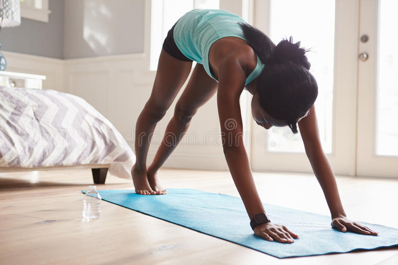 Young black woman in the downward-facing dog yoga pose royalty free stock photography