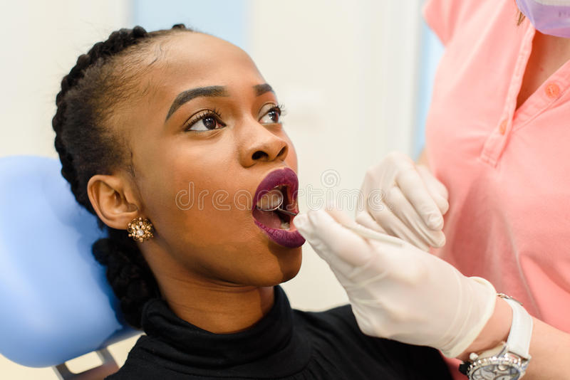Young black woman with female dentist doctor during tooth examination and treatment.  stock photo