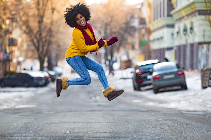 Young black woman is jumping in the middle of the street stock photo