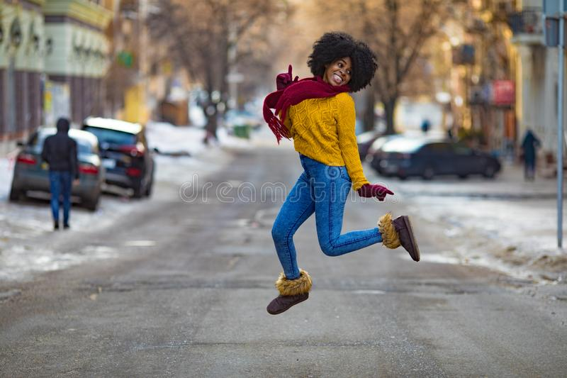 Young black woman is jumping in the middle of the street royalty free stock photography