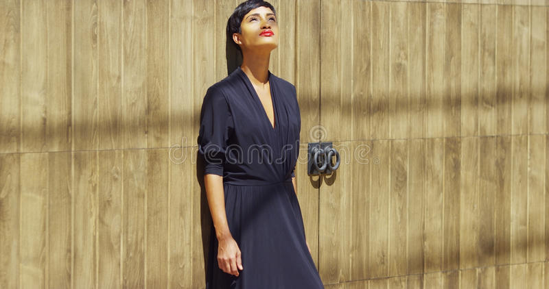 Young black woman leaning against wall in sunlight stock photo