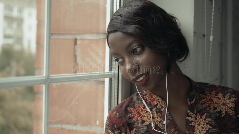 Young black woman listening music travelling looking outdoor the window, pensive - thoughtful, thinking future, music royalty free stock photo
